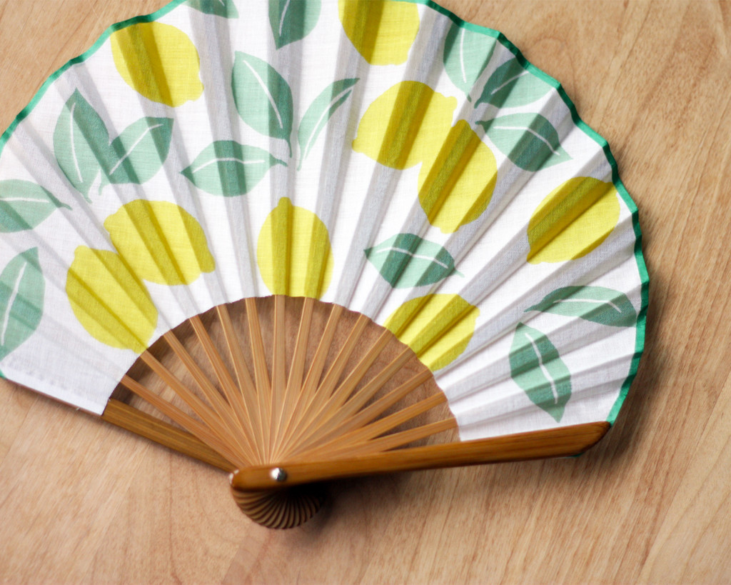 夏らしいレモン模様の扇子を広げた様子