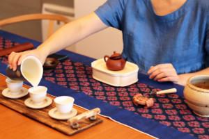 茶芸師が台湾茶を茶杯に注いでいる様子