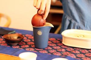 茶芸師が台湾茶を器に注いでいる様子