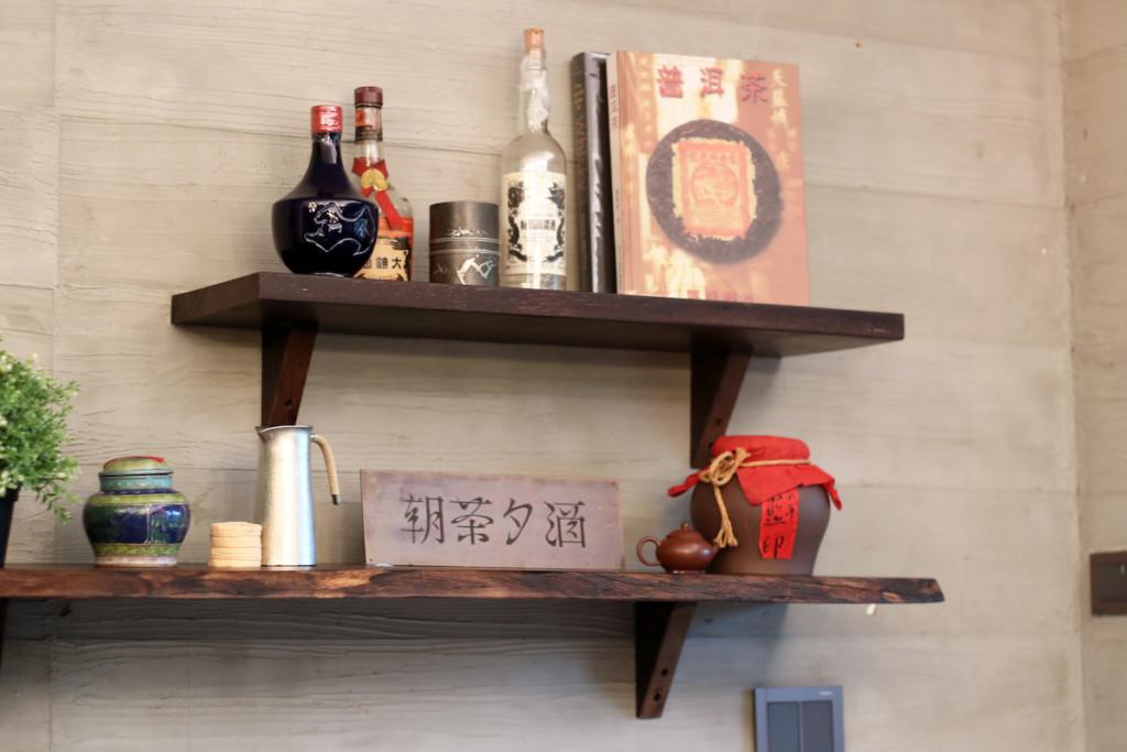 飾り棚に並んだ調度品とお酒とお茶の本