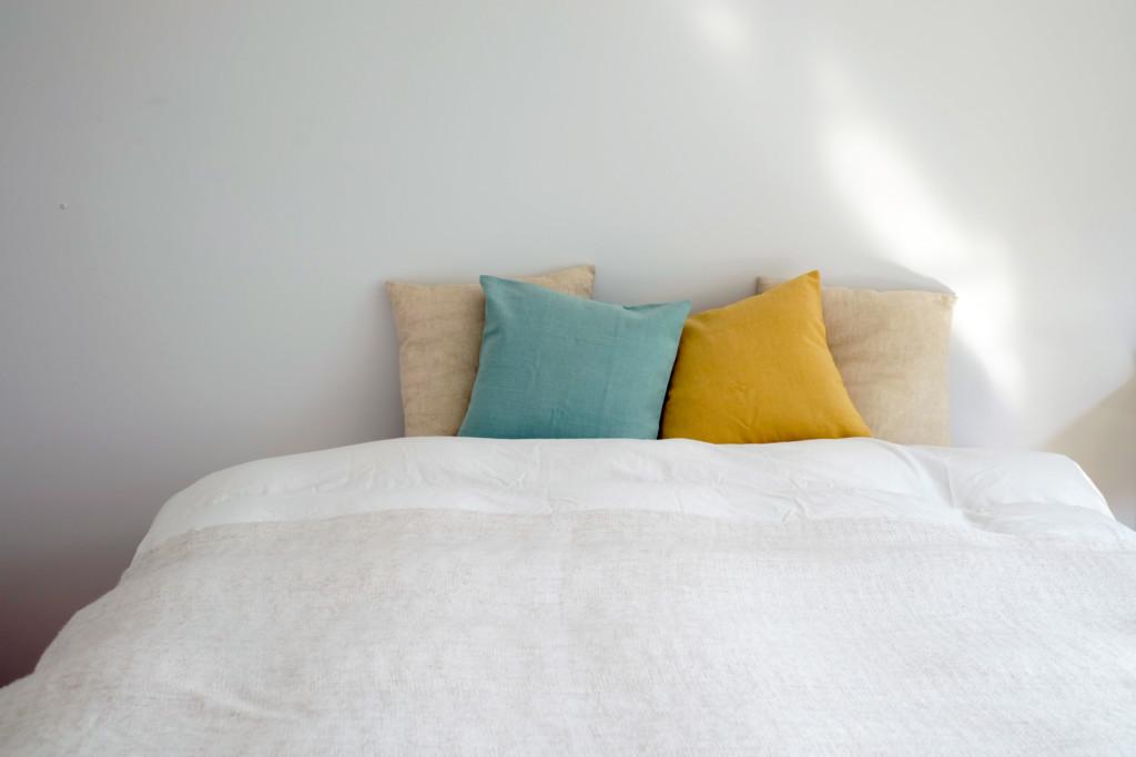 白いベッドとカラフルなクッション