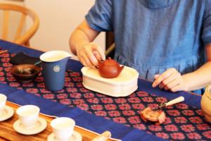 茶芸師が台湾茶を器に注ぐ準備をしている様子