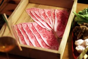 木の箱に盛りつけられた薄切りの牛肉