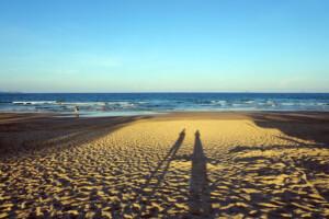 海外ビーチの砂浜にうつる夫婦ふたりの影