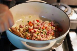 鍋で豚肉と香味野菜を炒めているようす