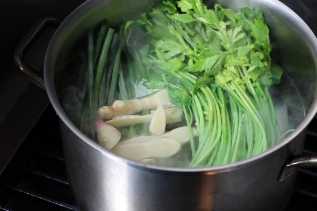 大きな鍋でネギ、セロリ、生姜が煮込まれているようす